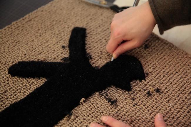マットの検品作業は五十嵐さんが担当。不要な糸をカットし、猫のかたちを整えていく