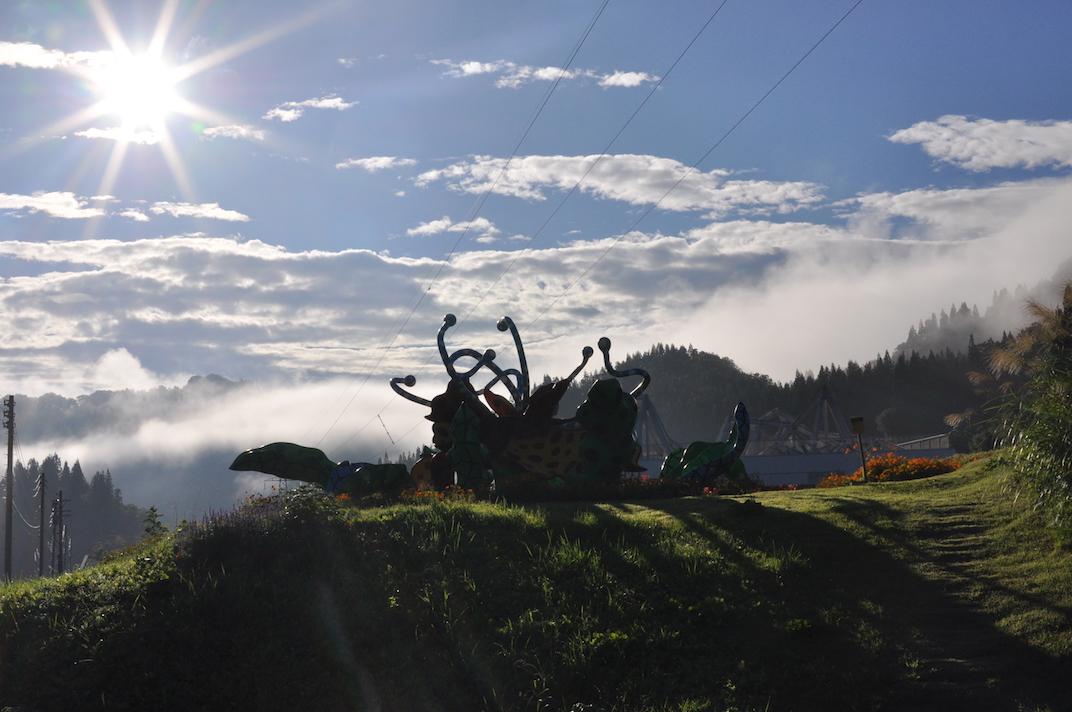 早朝、朝靄につつまれる松代の山並みと夏の爛々とした日差しを浴びる草間彌生《花咲ける妻有》。美しい朝。