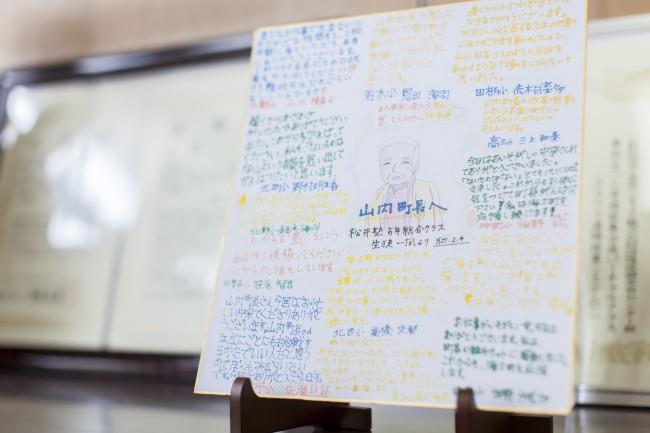 山内道雄町長。軽快で楽しい話しぶりがひとを惹きつける / ひんぱんに全国各地を巡っている。町長室には島外の子どもたちからの寄せ書きもあった