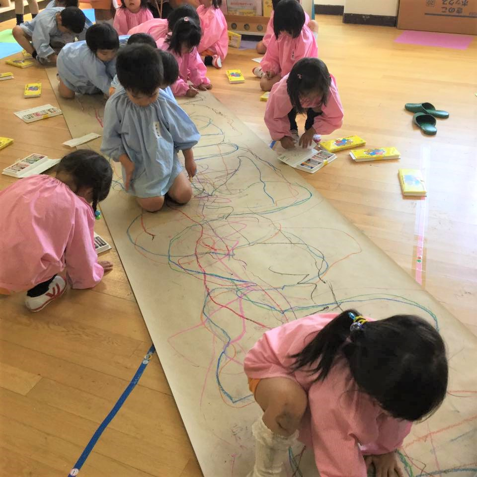 壁や床の画用紙に夢中で絵を描く子どもたち。