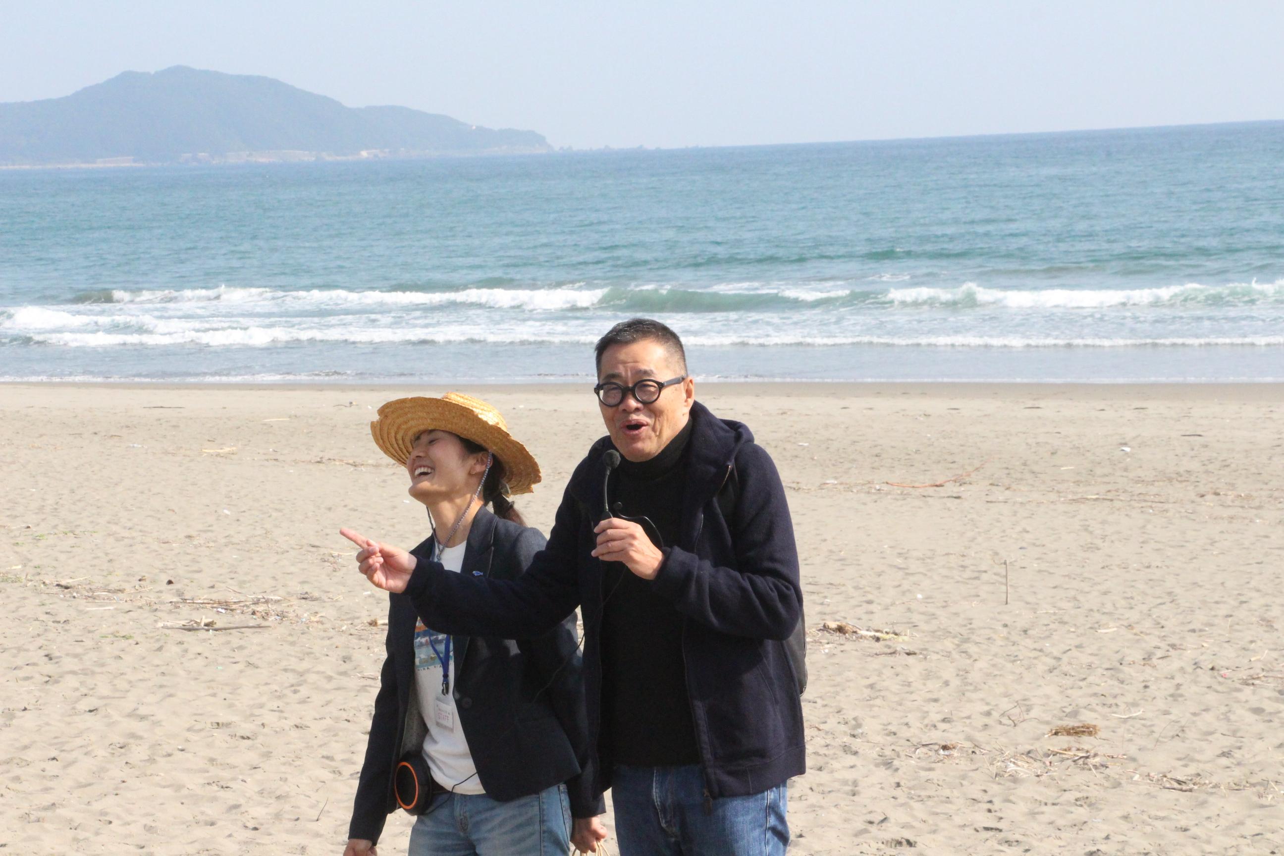 砂浜美術館の説明をする梅原真さんと学芸員のN村さん。