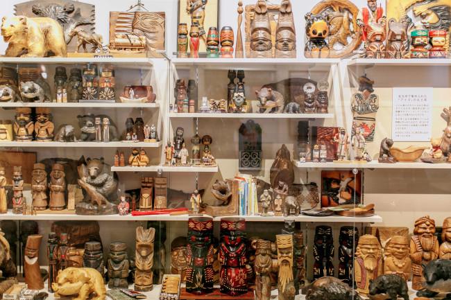 北海道大学総合博物館の2階には、各学部の「最新の一押し研究」が常設されている。これはアイヌ・先住民研究センターの展示。「今回の展示では、「アイヌ」をモチーフとするお土産を紹介します。ここに展示されているモノの作り手は、アイヌ民族に限定されません。そのため、展示タイトルのアイヌという言葉には、カギ括弧「 」を付けました。「アイヌ」のお土産は、様々な視点から考えることができます」とある。木彫りの熊と再会