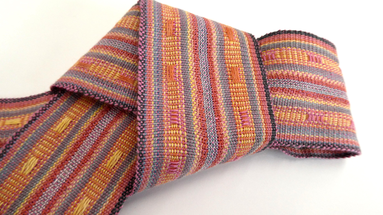 写真中央の衣装の帯・襟・袖口。経緯浮き織り(帯の中央部分は紗織り)。すべて天然染料により染色。