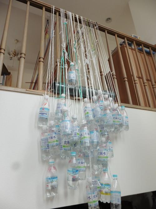 又吉さんの自宅で作品を織っている様子。織り機から出た糸は重りであるペットボトルにつながっている。