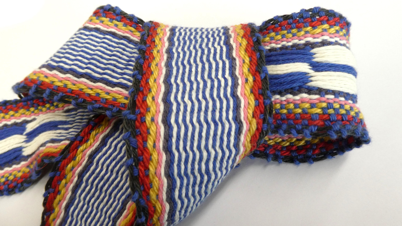 左の衣装の帯。腰端織りと経浮き織り。沖縄の海を表現。