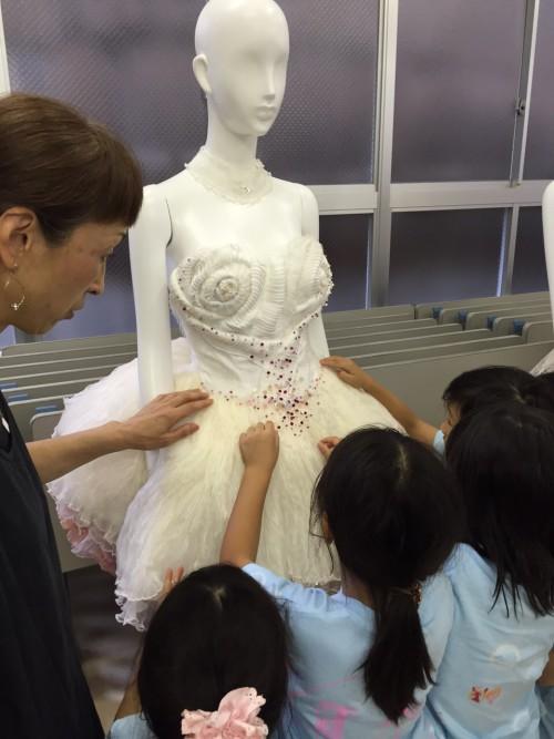 デザインの専門学校でドレスを触る子どもたち