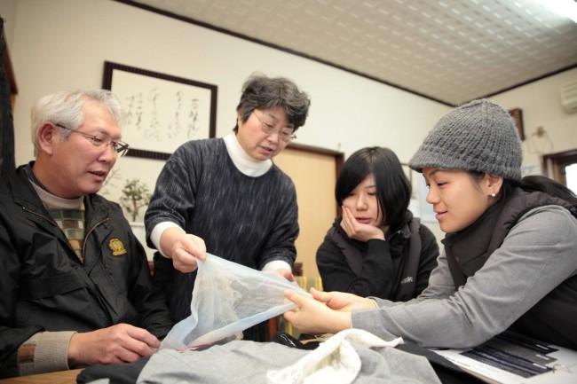 立川織物の立川治秀さん(左)と奥さん(中央)、エフスタイルの2人。「からみ織」というガーゼのような織り地に2人は興味津々