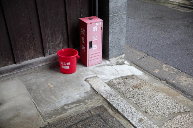 路地の入口に置かれた消火バケツと消火器。防災の心がまえを路地のみんなで共有している心強さ