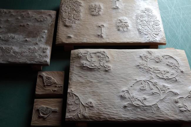 貴重な版木の数々。嘉戸さんが自らデザインすることもある。左下の雀2匹は、チャリティーのアートイベントで出合った須田悦弘氏が自ら彫ったもの。右奥の鍵モチーフが斬新な版木はミヤケマイ氏と展覧会用に共作したものだ