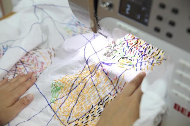 デザイン室の壽浦(じゅうら)直子さん。利用者の縫ったシャツにミシンをかけ、素晴らしいコラボレーションを仕上げる