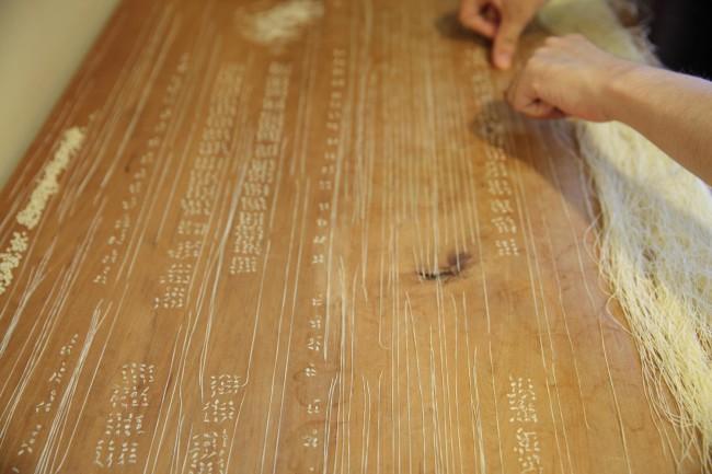 吉本篤史さん。とにかく糸が好きで、布の工房では糸のインスタレーション(としか言いようがない)を制作し、自室の机の上も展示スペースのようである