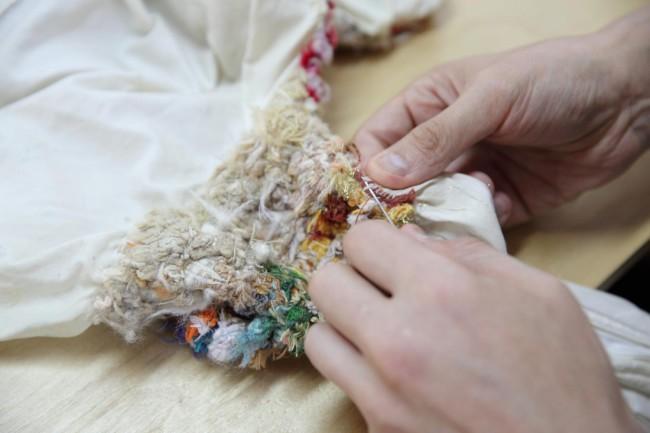 布の工房で制作する野間口圭介さん。圧縮していくような、独特の運針と糸づかいが不思議な美しさだ