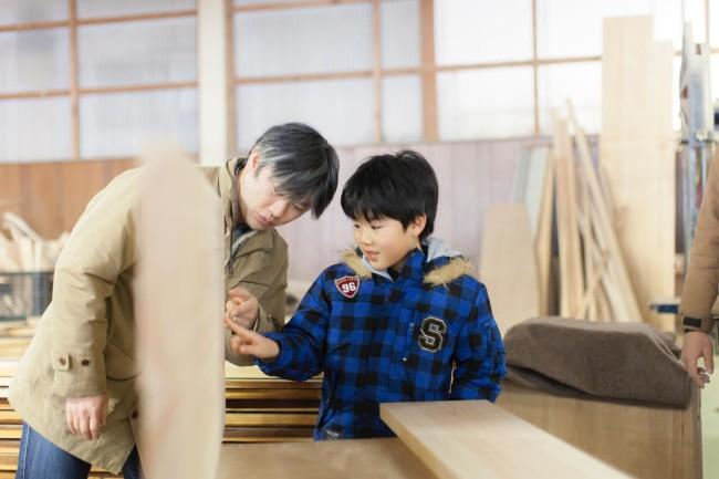 学習机ツアー参加者の親子。天板のどちらを机の表側にするかを父と子で相談中