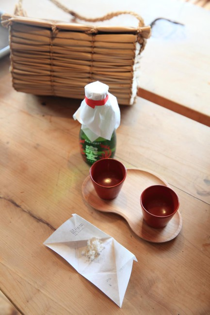 (上)その日の朝に神主の細川一郎さんが集落から取って来た榊を剪定し設しつらえる(下)田んぼに神さまをお送りするときに使う塩やお神酒を入れるためにつくった荷俵にどら。能登の朝市で使われているガマの穂のかごを集落のおじいちゃんにこぶりなサイズでつくってもらった