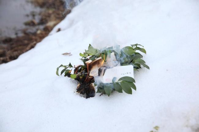 まるやま組の依り代は、毎年1年間のモニタリングで観察できた植物や生物の総覧を小さな文字で記載し、土地の多様性の全体像を表現している。表紙の数は観察総数で、378、395、419、そして今年は423と、年々増えている。参加したひとりひとりの願いを依り代に託し田んぼの畦で炊き上げて、アエノコトの一連の祭礼は終わる