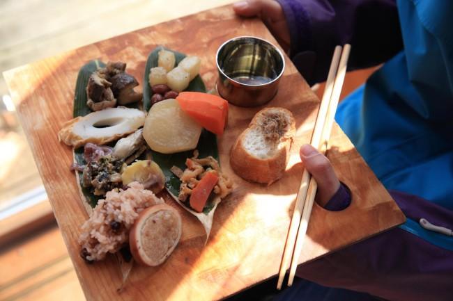 (上2点)それぞれの持ち寄ったお手製料理や土地の食べ物がオープンキッチンを彩る。能登ヒバの間伐材でつくったパレット型のプレートに裏山で採った笹を敷き、季節の色を置くように盛りつける