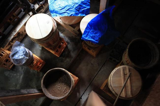 (上)谷川醸造当代、谷川貴昭さん(下)まるやま組の「あぜ豆醤油」本醸造仕込み。1年もの、2年もの、3年ものと仕込んだ年数によって杉樽が異なる