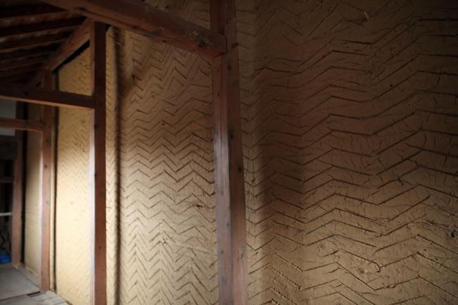 崩落した土壁をすべて撤去し、木舞からつくり直した土蔵の土壁。手打ち、大直し、たて縄入れ、よこ縄入れ、何層も土が塗り重ねられている。サヤに囲まれたこの土蔵では、風雨にさらされる心配がないので、この段階で当面の修復を終えた。将来、余裕ができたら中塗り、漆喰仕上などを施していく予定
