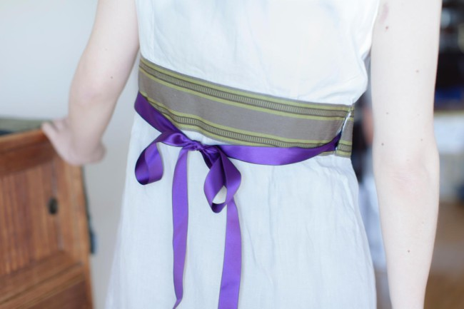 大人っぽいカシュクールワンピース。グレーのリネン生地が足りず、白の木綿と組み合わせた。縞のリボンはスウェーデン製。差し色のリボンの紫が映える。行司さんの服にはリボンがよく使ってある