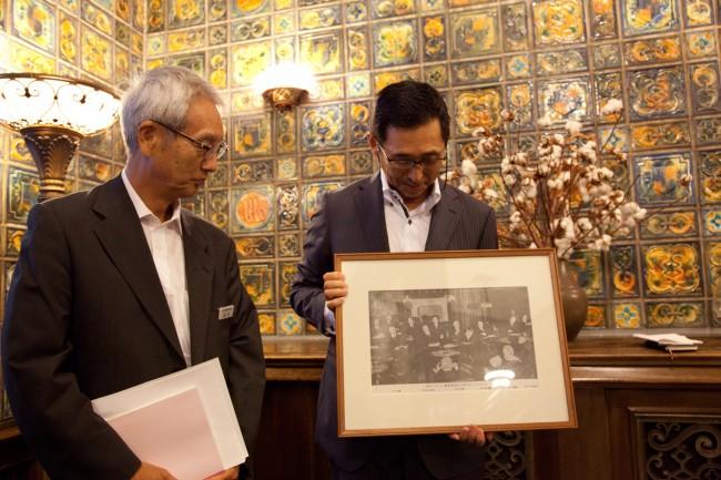 リットン調査団が使用した当時の写真とともに。日本綿業倶楽部の総務部長の品川和三さん(左)と事務局長の槙島昭彦さん(右)