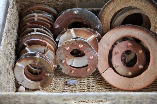 拠点のひとつ、久美浜にて。海で拾いものをし、廃棄処分となったカキの殻を焼きものに使う。窯では地元の土を使った器なども制作している。焼くときに用いる器を固定する道具や置き板のかたち、変化もまた美しい