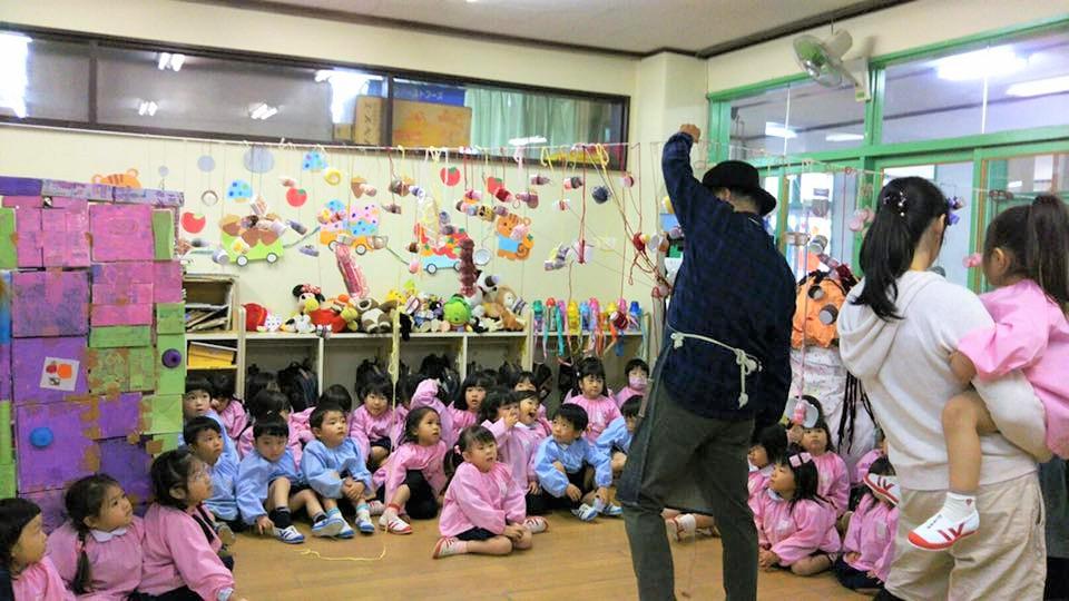 幼稚園で行ったワークショップで子どもに囲まれる水野さん。