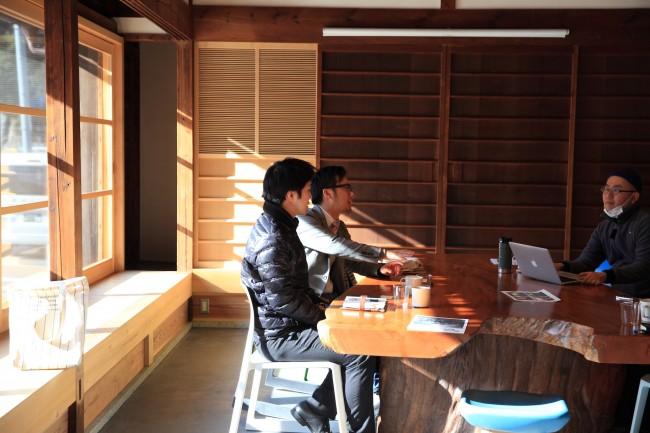 高見川のほとりに佇む大きな民家を改修した / 「オフィス」と「キャンプ」を併せてみたら? という発想から名称が決まった / 地元の木材を使ったテーブルで、打ち合わせや作業をする