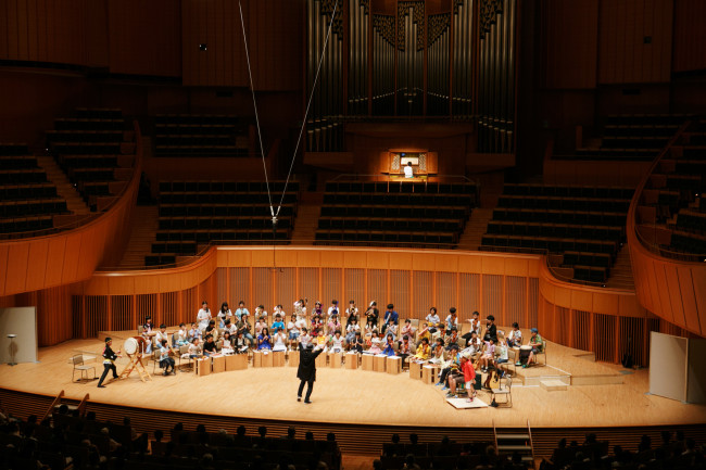 札幌コンサートホールKitaraにて。小学生から18歳くらいまでがメンバーのさっぽろコレクティブオーケストラ。大友が最初は「指揮者」を演じるが、時にその姿は中心から消える