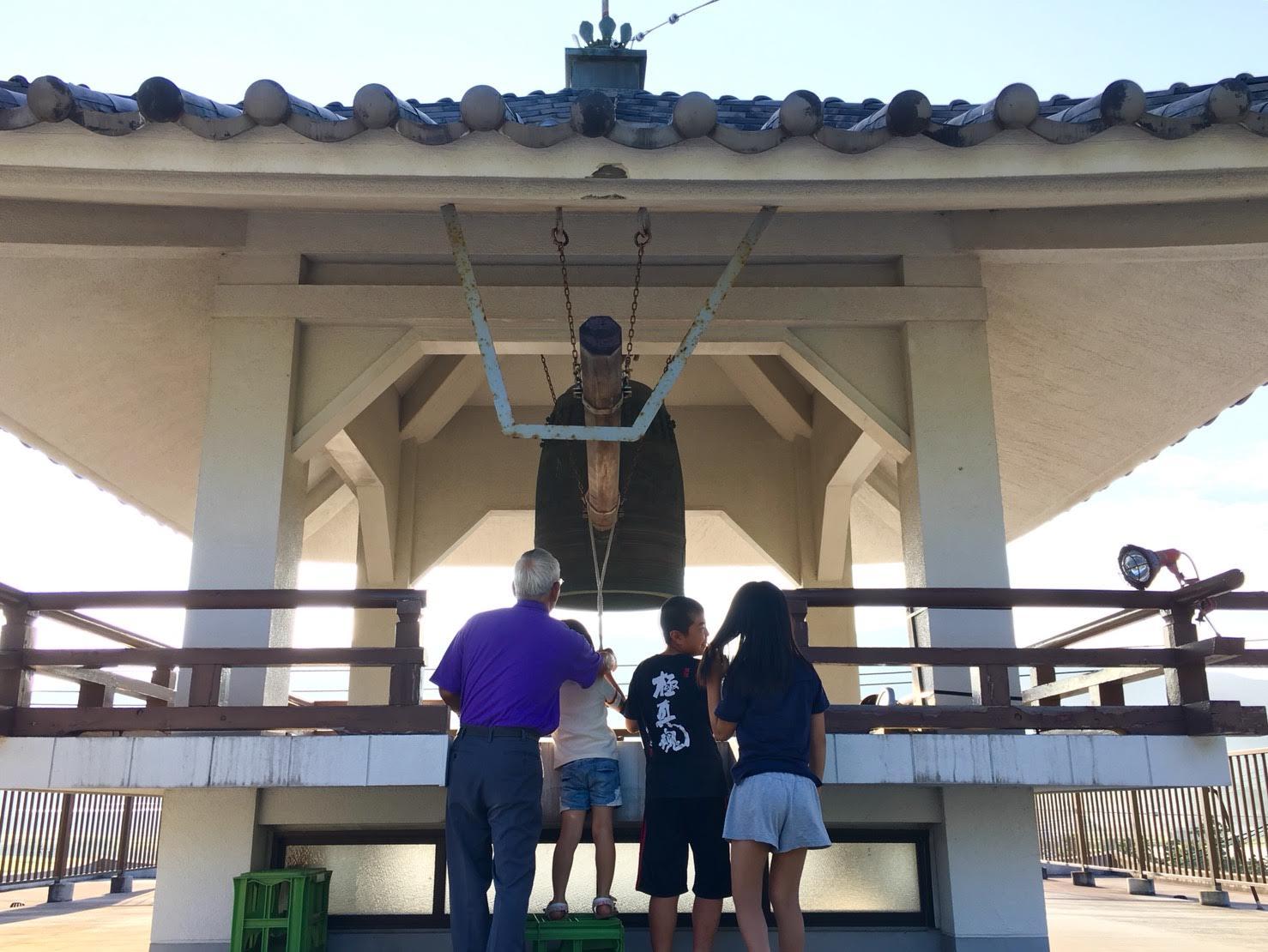 夏休みのラジオ体操のあと、明信寺の鐘をつく子どもたち