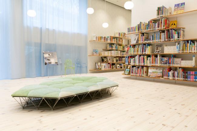 こんもりとした丘が連なるような建物 / 雑誌が並ぶ1階のブラウジングコーナー / 3階の絵本・児童書コーナー。利用者は高校生や親子連れが目立つ