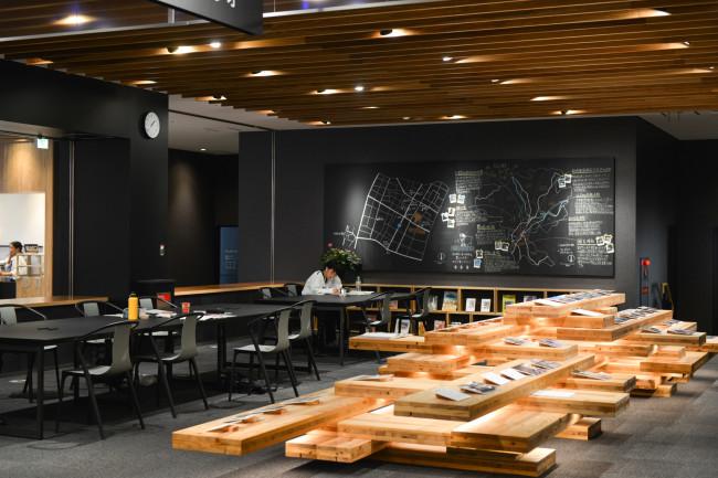 1階のコーナーいくつか。プレススタジオは「表現する場所」。特に地域や社会の資産にもなるような表現活動の支援を行う。奥に見えるのは簡易自動製本機、通称エスプレッソ・ブックマシーン。オリジナルの冊子制作に使う / 都城市全体と図書館周辺を拡大したまちなかエリアの2つの地図を描く「地図黒板」。この前で話し合いを行ったり、チョークで情報を書き込んだりも