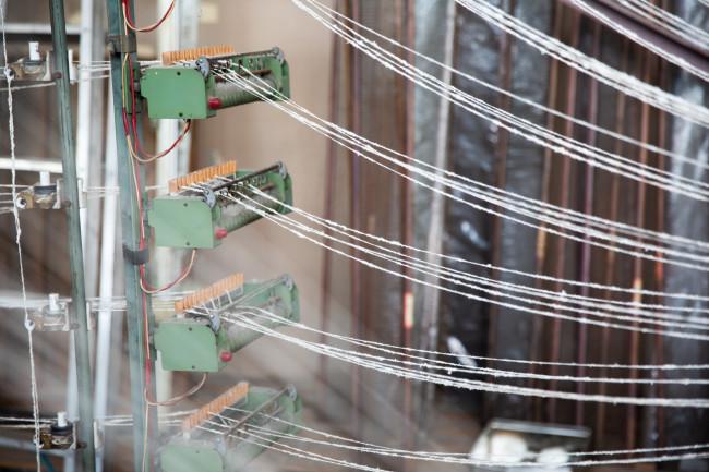 宮浦晋哉さんが運営する「セコリ荘」にはさまざまな産地から集めた、テキスタイルのサンプルが並ぶ / 織物の経糸を作る機械「整経機」