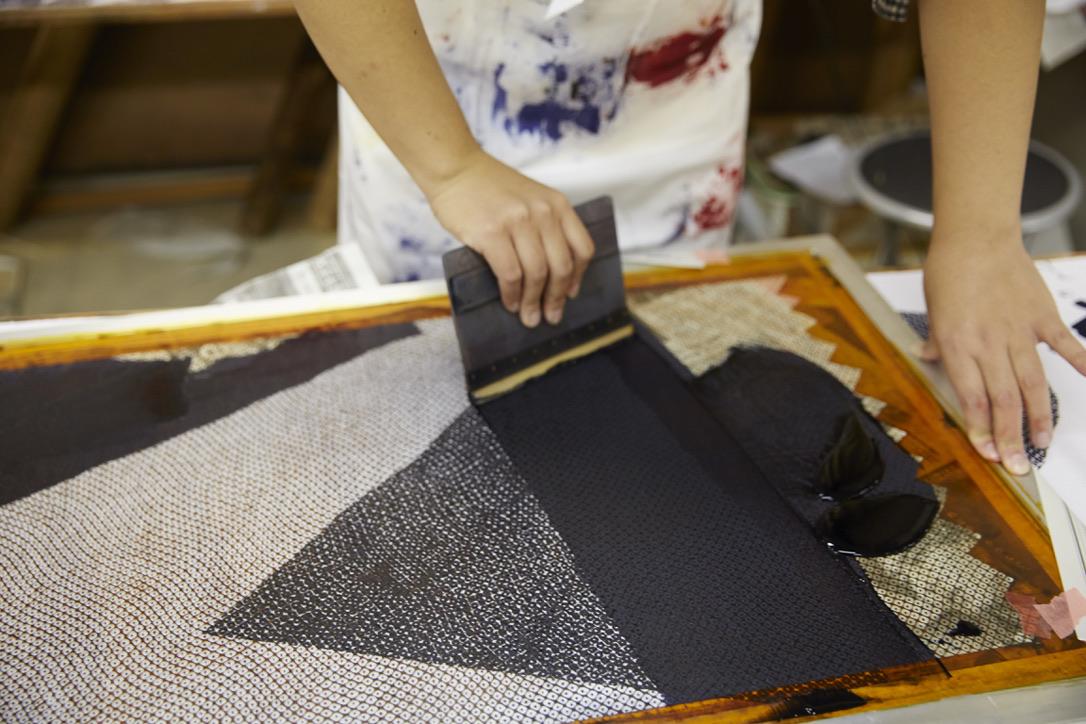 紙にデザインを下描きして、型紙を使って布を染め上げていく