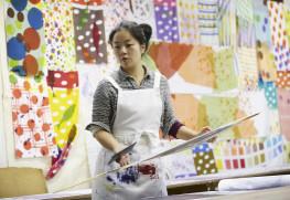 生地を染める山元さん。壁一面に色鮮やかなケイコロールの布地が貼られている