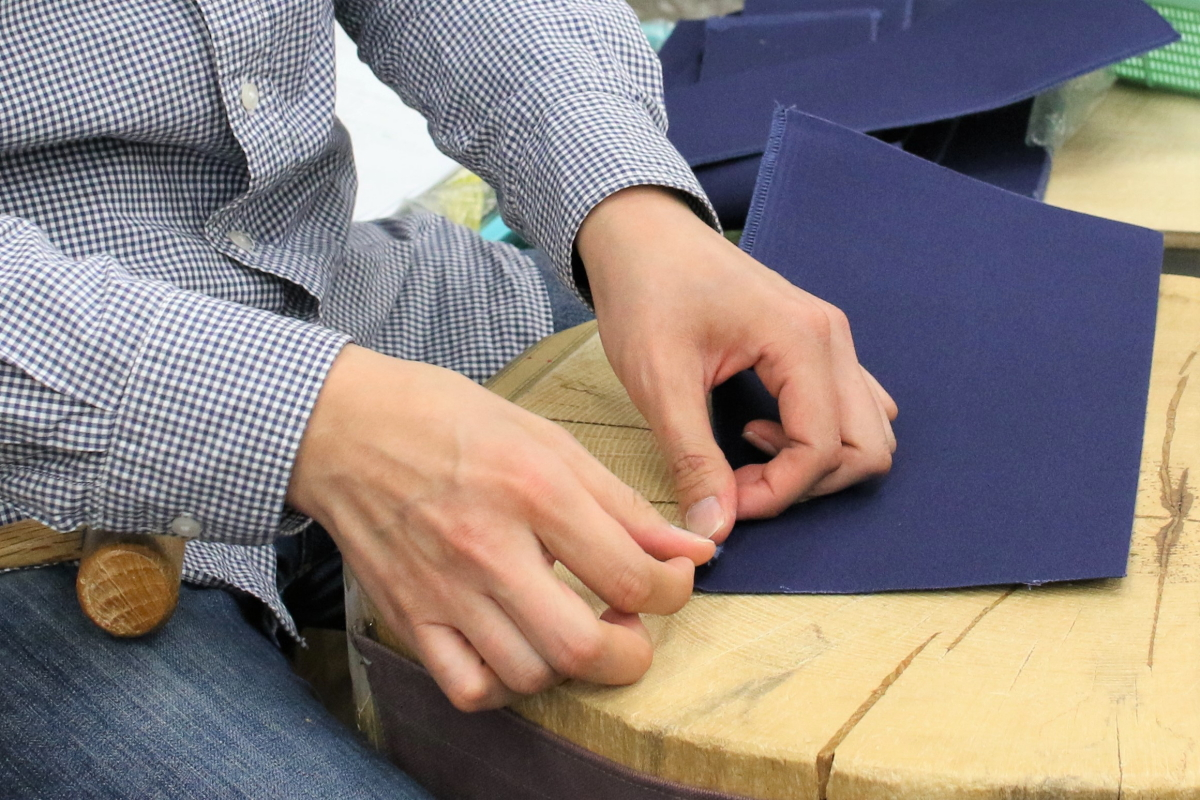 下職がハンマーを使い、固い帆布に折り目をつけている様子。作業台は大きな切り株