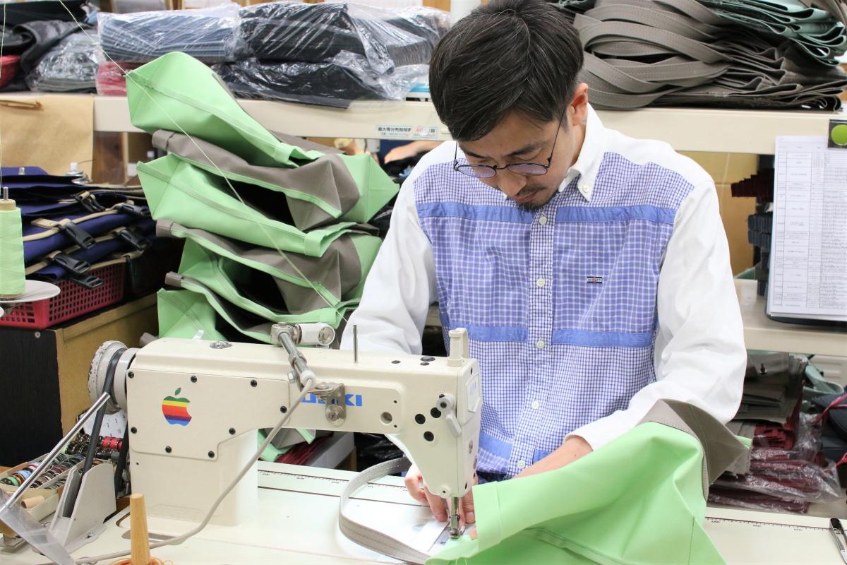 工房のミシンでかばんを縫う竹内さん