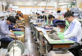工房内の様子。ミシンを使う職人(右側)と、帆布に折り目をつけたりする下職(左側)が二人一組になってかばんをつくる