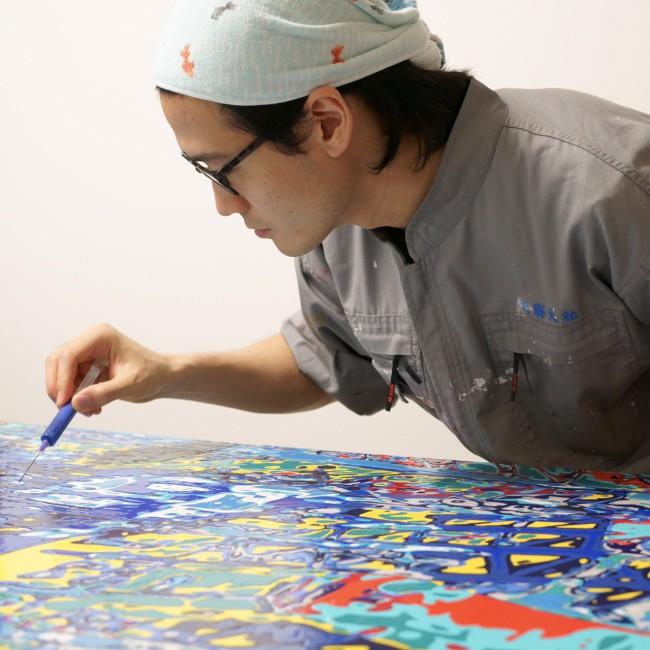 現在の技法で描く近藤さん。絵の具のつまった注射器を、筆を立てるように持ちながら色を落としていく