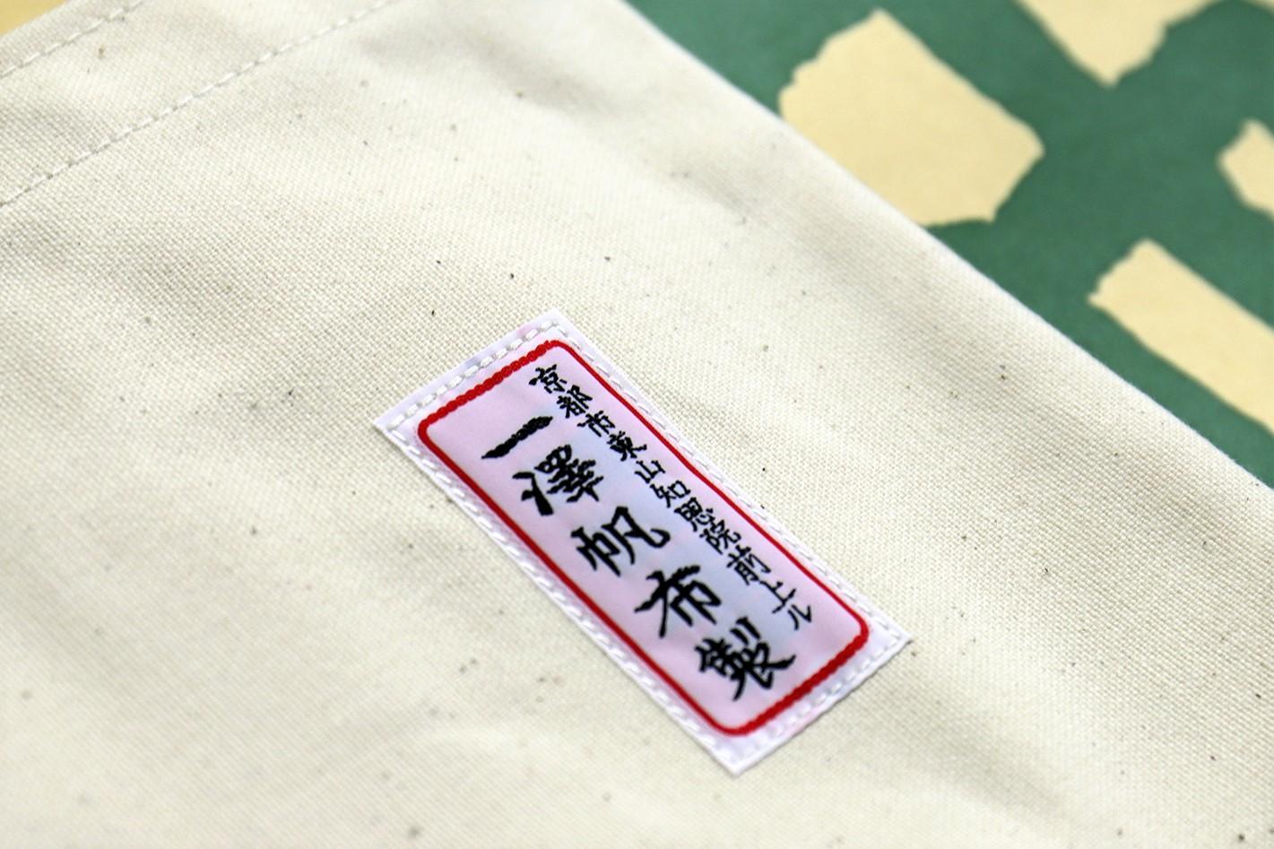 まっすぐな縫い目でカバンに縫い付けられたネームタグ