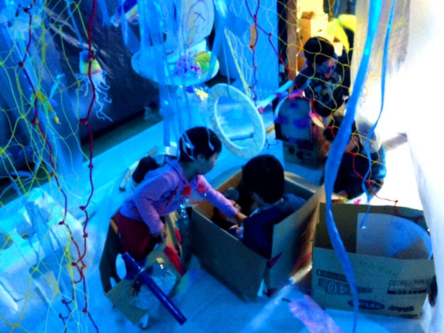「海の中を冒険しよう」八日市アトリエワークショップ。薄暗い部屋は深海の世界。どんな世界かみんなで想像しながらつくっていく。魚も潜水艦もアクアラングも大切な深海のアイテム