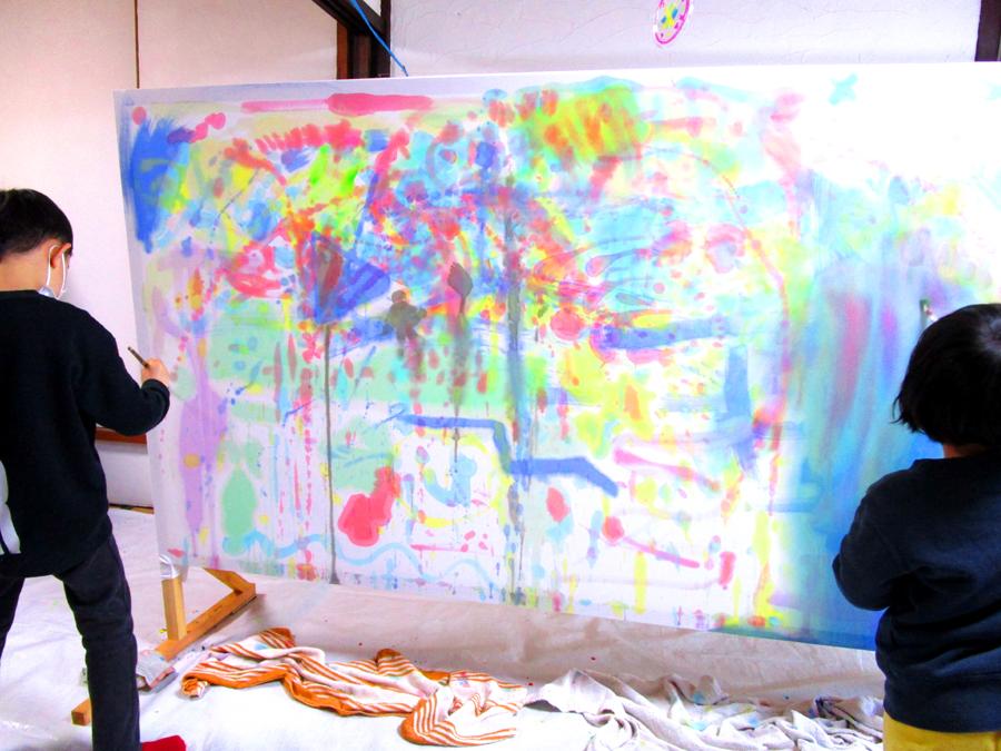 白い布に光る絵を描こう」八日市アトリエワークショップ。真っ白い大きな布に絵具を塗れば不思議な光る絵が現れた