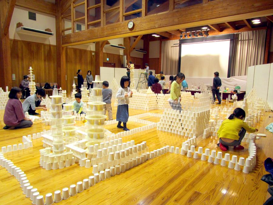 「10000個の紙コップで遊ぼう」地域ワークショップ。10000個の紙コップと20000個の透明プラスチックコップ、いろいろなかたちの発泡板を駆使して思い思いの立体物を作成