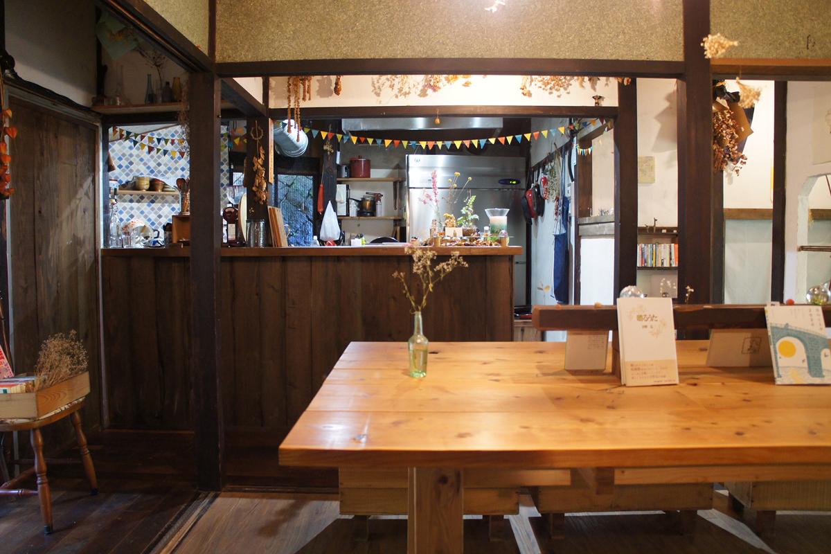 (cap)店内には、大きなテーブルが1つと2名掛けのテーブルが2つ。机のサイズは、心地よいと思ってもらえる大きさになるよう、町田さんが設計した。本や雑貨、植物など、インテリアの組み合わせの妙も楽しい