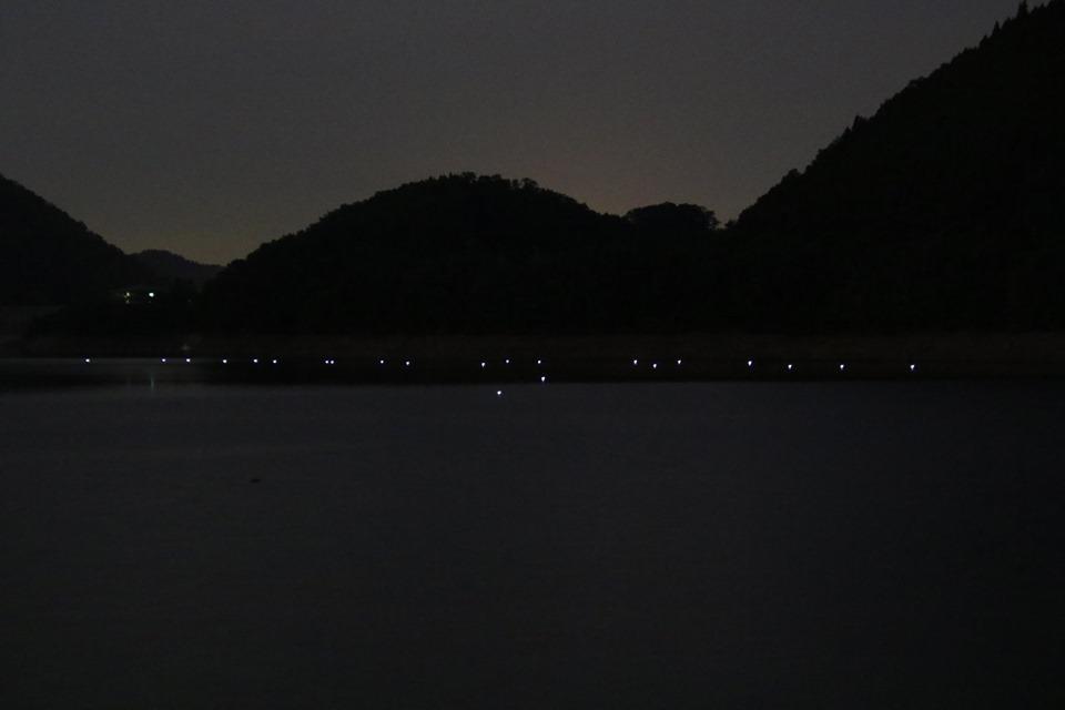 """天若湖の湖面に明かりを灯す""""あかりがつなぐ記憶""""のようす。ひとつひとつの明かりの位置は、ダムの建設によって沈んだ民家を示している"""