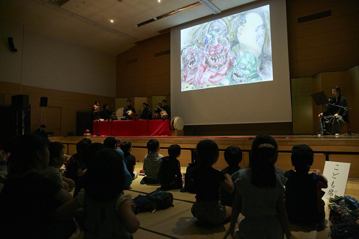 若獅子会が伝統的な邦楽囃子と創作曲の演奏に加え、松井さん作画の紙芝居「桃太郎」に音楽をつけて上演した(2019年『CAC』於:明治神宮参集殿)