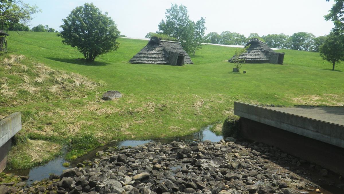 水場の祭祀場の遺構(手前)と復元された竪穴住居
